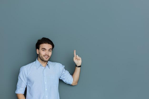 Buscar. hombre creativo positivo alegre de pie contra el fondo gris y sonriéndole mientras apunta hacia arriba con su dedo