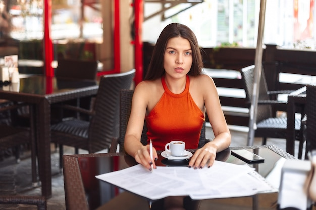 Business lady girl se sienta en una mesa en un café, considera papel, piensa. reanudar, firmando un importante negocio. trabaja fuera de casa.