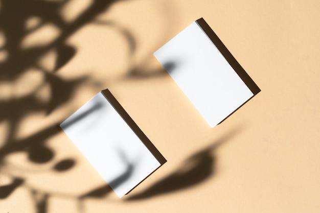 Businesscard blanco en blanco sobre fondo beige con sombra floral creativa