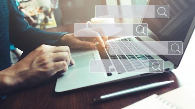 Búsqueda y conceptos de big data con mano masculina usando computadora portátil en cafetería con signo de icono de motor de búsqueda.