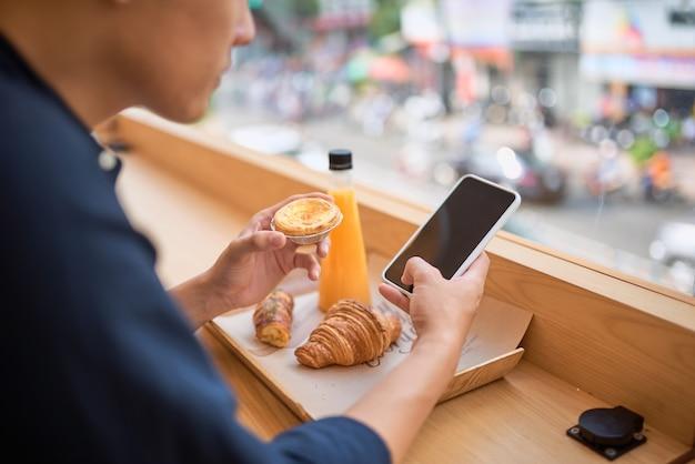 Las búsquedas masculinas necesitaban información en el sitio web de internet a través de un teléfono inteligente mientras se sentaban en la terraza del café con jugo y postre dulce