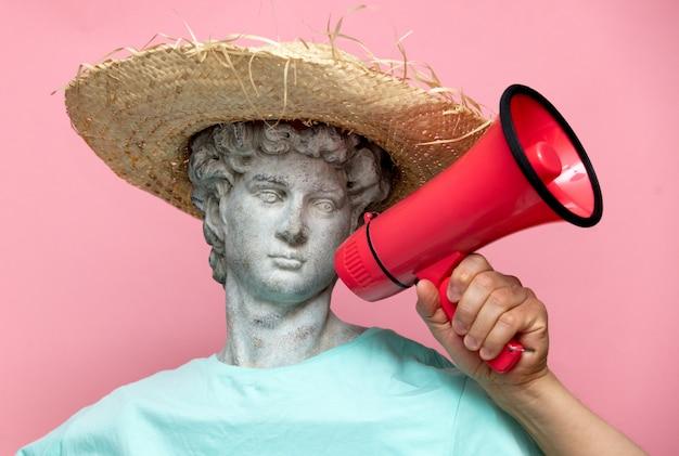 Busto antiguo de hombre en sombrero con megáfono rojo sobre fondo rosa