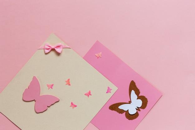 Butterfliy figyrines en el fondo de papel rosa