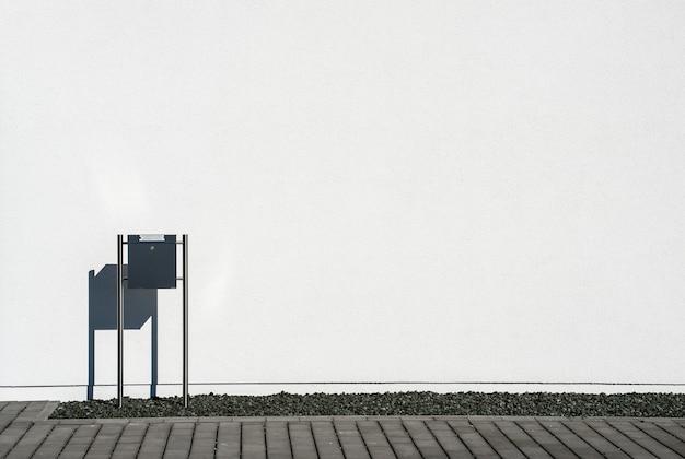 Buzón negro delante de un muro de hormigón blanco