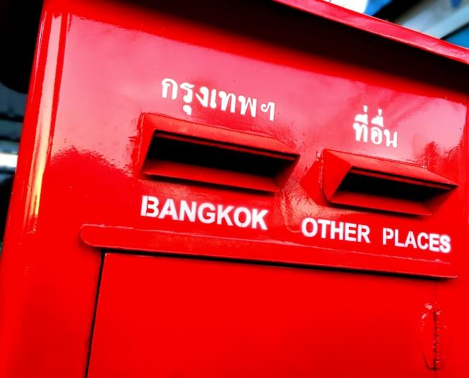 Buzón rojo vívido con textos de destino en inglés y tailandés