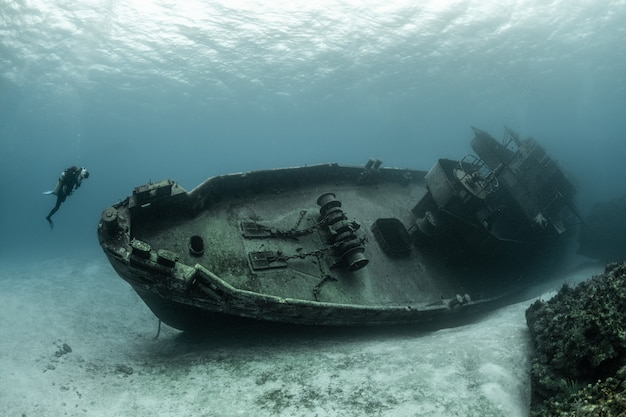 Buzos examinando el famoso submarino uss kittiwake hundido en las islas gran caimán