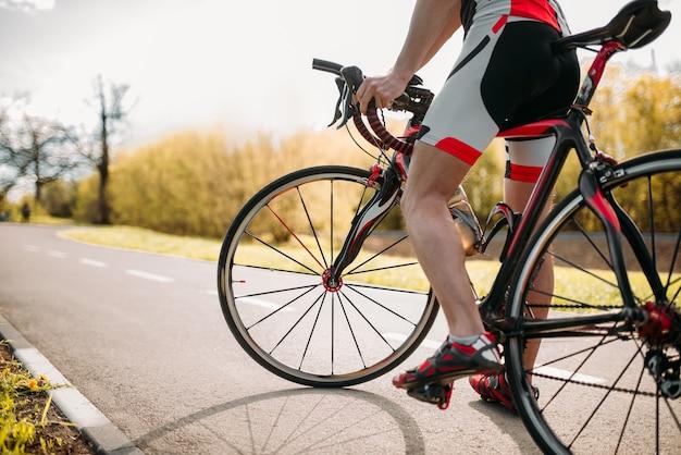 Bycyclist en casco y ropa deportiva en bicicleta