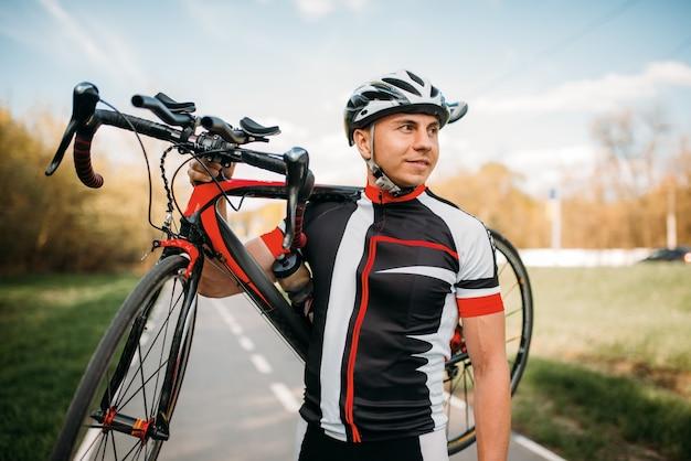 Bycyclist mantiene la bicicleta sobre el hombro después de andar en bicicleta