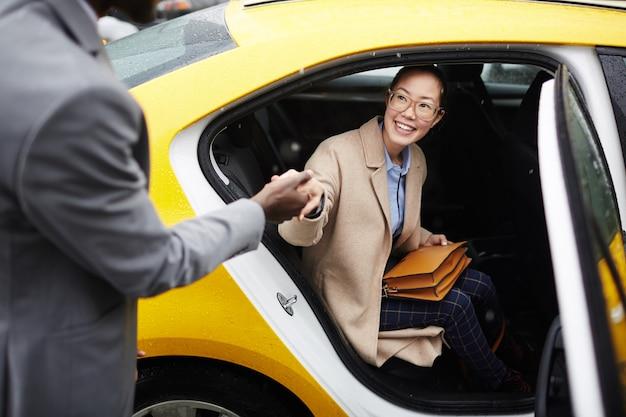 Caballero ayudando a mujer joven a salir de taxi