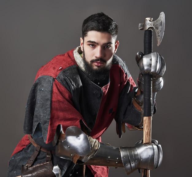 Caballero medieval en gris. retrato de brutal guerrero cara sucia con armadura de cota de malla ropa roja y negra y hacha de batalla