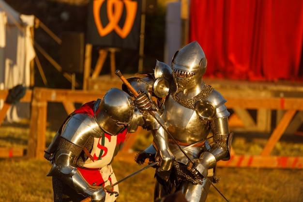 Los caballeros con armaduras medievales luchan en el torneo de verano. foto de alta calidad