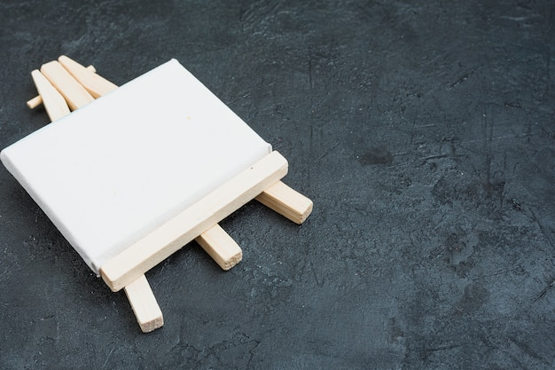 Caballete de madera miniatura en blanco sobre fondo de pizarra pizarra negro