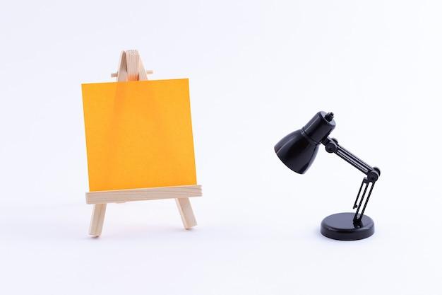 Caballete en miniatura de madera con lienzo cuadrado de colores en blanco y lámpara de mesa