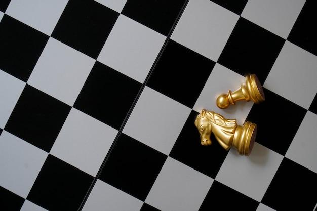 Caballos y peones sobre papel de ajedrez.