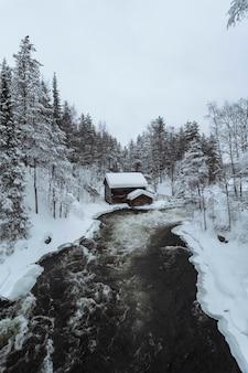 Cabaña cubierta de nieve por río en el parque nacional oulanka, finlandia