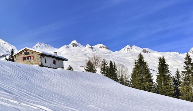 Cabaña en la hermosa montaña nevada bajo un cielo azul