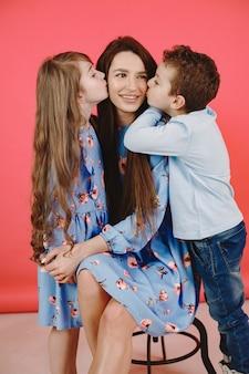 Cabello largo en niñas. ropa azul. hija e hijo besan a mamá.