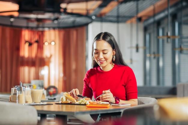 Cabello largo y oscuro atractiva mujer joven elegante con cabello largo y oscuro almorzando en el restaurante