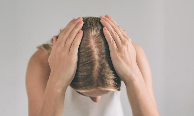 El cabello de las mujeres es un primer plano de la vista superior. la mujer rubia lleva la camisa aislada en blanco.