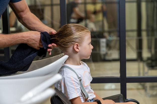 El cabello de un niño se seca con una toalla después de lavarse el cabello antes de cortarlo.