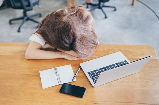 Cabeza agotada frustrada de la mujer abajo en la tabla. finanzas del logro y concepto del negocio