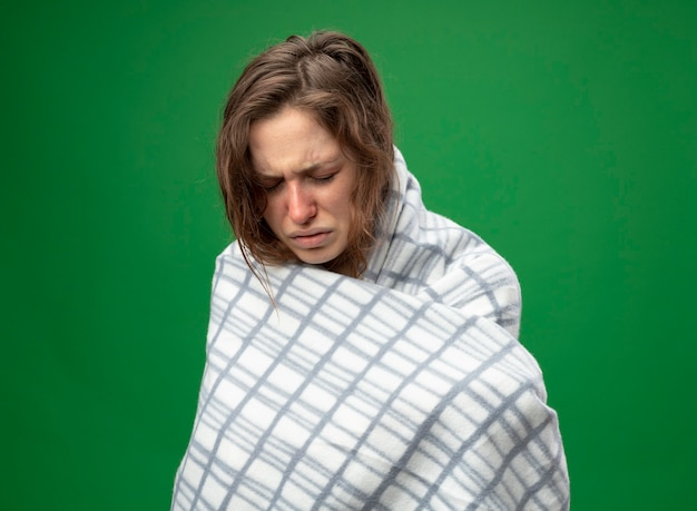 Con la cabeza baja débil joven enferma vistiendo túnica blanca envuelta en cuadros aislados en verde