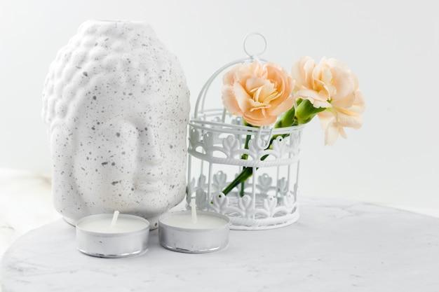 Cabeza de buda figurilla de cerámica blanca, jaula decorativa con flores y velas.