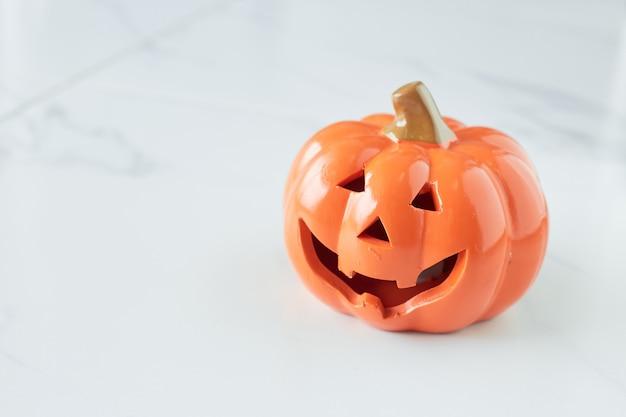 Cabeza de calabaza de halloween jack linterna en el piso de mármol blanco
