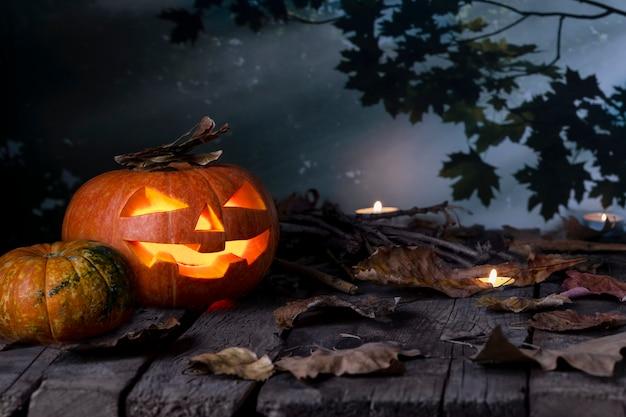Cabeza de calabazas de halloween jack o linterna y velas en la mesa de madera en un bosque místico en la noche. diseño de halloween