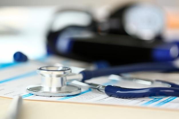 Cabeza de estetoscopio y bolígrafo plateado en formulario de solicitud médica