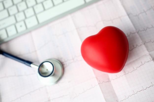 Cabeza de estetoscopio médico y corazón de juguete rojo