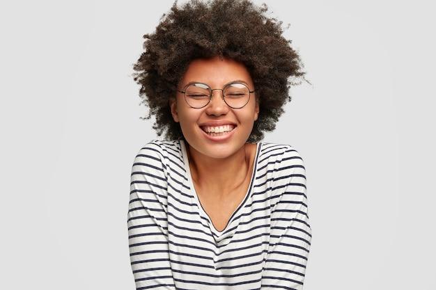 En la cabeza de la hermosa mujer sonriente divertida de piel oscura tiene un corte de pelo afro, se ríe de algo, mantiene los ojos cerrados de placer, vestida con un suéter a rayas, aislado sobre una pared blanca. felicidad