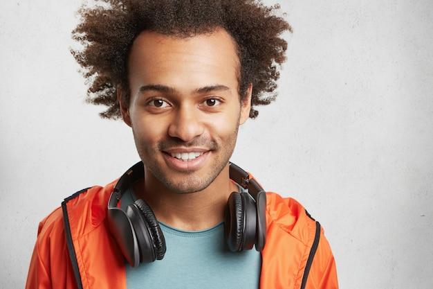 En la cabeza de un hombre guapo de raza mixta con pelo tupido, tiene buen humor