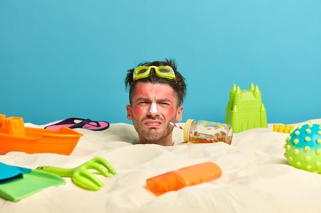 Cabeza de hombre joven con crema de protección solar en la cara rodeada de accesorios de playa