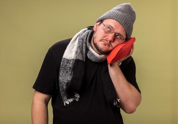 Cabeza inclinada débil mirando hacia arriba de mediana edad varón enfermo vistiendo gorro y bufanda de invierno poniendo una bolsa de agua caliente en la mejilla