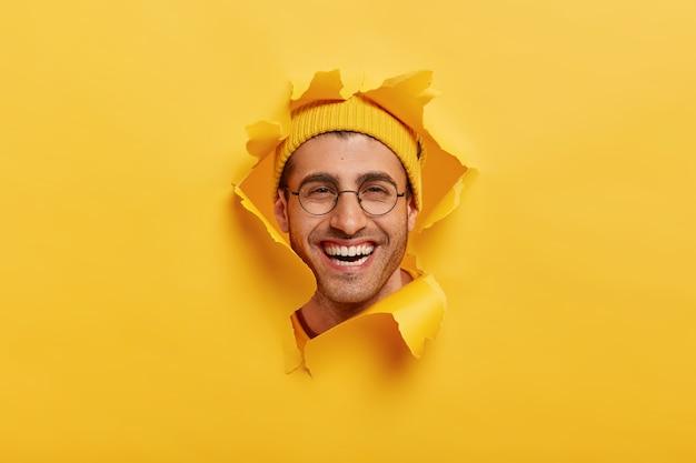 En la cabeza de un joven sin afeitar positivo sonríe ampliamente, lleva gafas ópticas redondas, casco amarillo