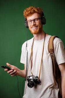 Cabeza lectora sonriente con barba hipster con mochila y cámara retro, escuchando música