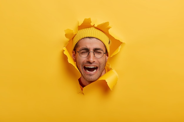 Cabeza masculina en el agujero de la pared de papel. hombre europeo desesperado que llora lleva gafas redondas y sombrero amarillo, expresa emociones negativas, mantiene la boca abierta