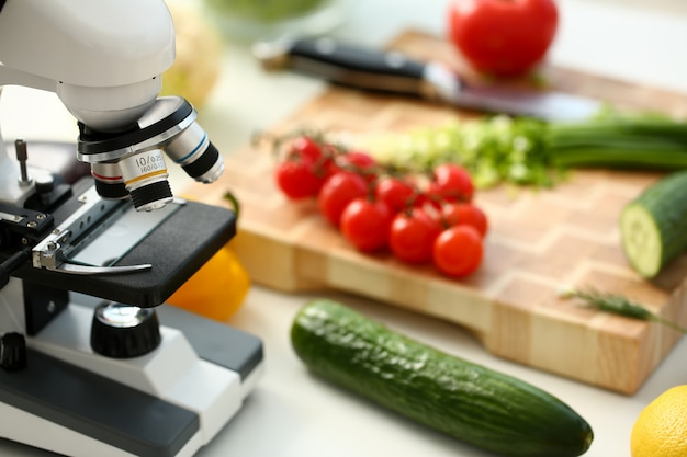 Cabeza de microscopio en cocina fondo verduras concepto nitratos