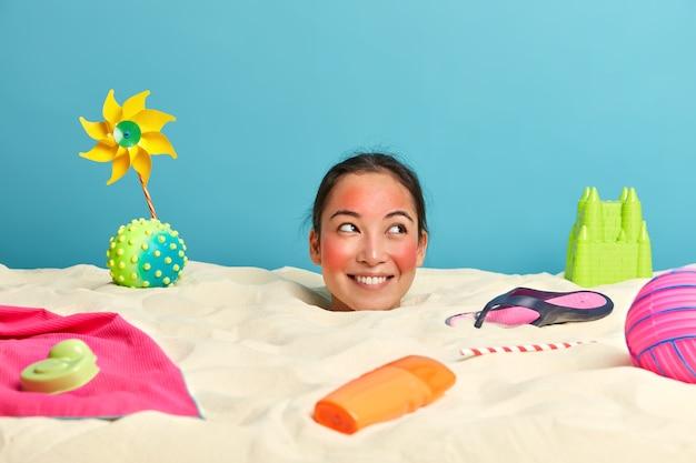 Cabeza de mujer joven con crema de protección solar en la cara rodeada de accesorios de playa