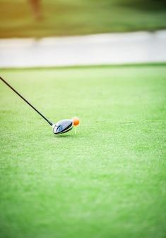 La cabeza del palo de golf de madera está a punto de golpear una pelota de golf sobre la hierba verde