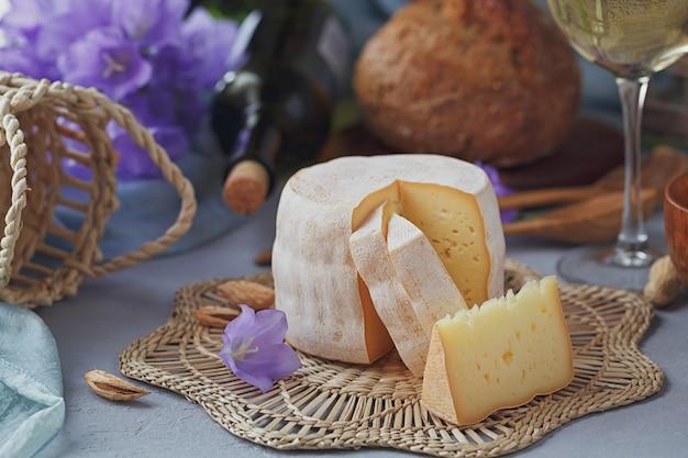 Una cabeza de queso fresco ecológico acompañada de pan, frutos secos, vino blanco y flores de verano. concepto de comida sana y orgánica.