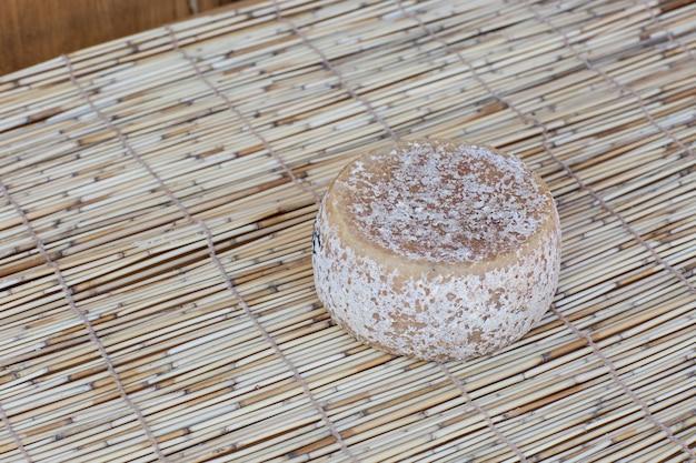 Cabeza redonda entera de parmesano o queso duro parmigiano en madera