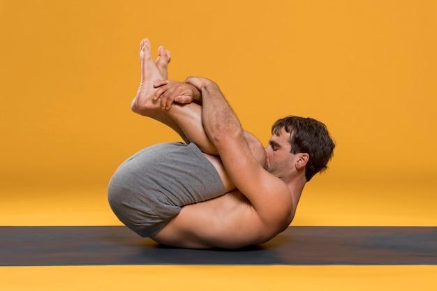 Cabeza a las rodillas posar sobre estera de yoga