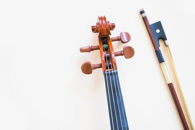 Cabeza del violín clásico con arco sobre fondo blanco