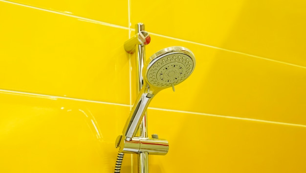 Cabezal de ducha sobre fondo de textura de pared de azulejos de cerámica amarilla