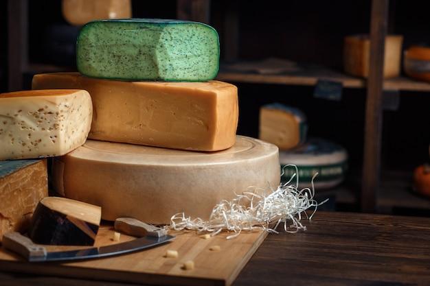 Cabezas de queso con rodajas y cuchillos sobre una tabla de madera con un interior