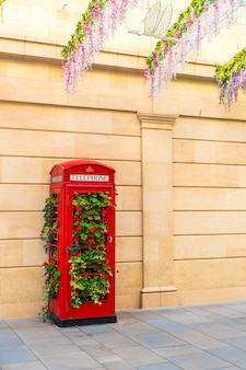 Cabina de teléfono roja famosa en londres con hojas