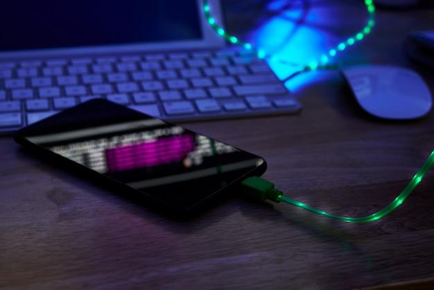 Cable de carga brillante en el teléfono inteligente acostado en la mesa de la oficina en la oscuridad