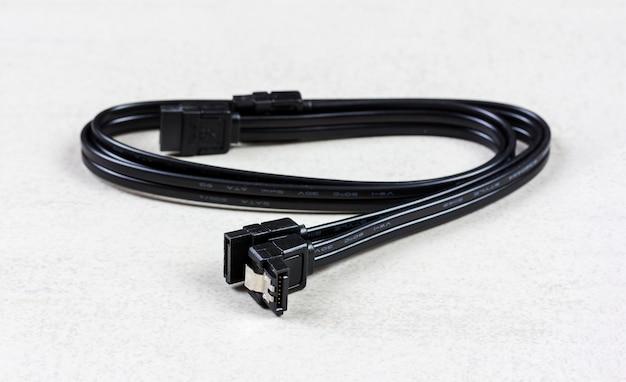 Cable de computadora negro serial ata 6gbs sobre fondo gris closeup